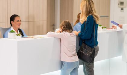 Mädchen im Krankenhaus-Wartezimmer stützt sich auf das Pult mit antibaktereller Oberfläche