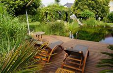Naturpool im eigenen Garten, der von einer weitläufigen Bambus-Terrasse von JAF umrandet wird.